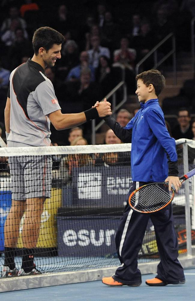 Novak Djokovic shakes hands with a young fan who stepped on the court to play against Djokovic in place of Andy Murray in the BNP Paribas Showdown Tennis Tournament on Monday, March 3, 2014, in New York. Djokovic won 6-3, 7-6