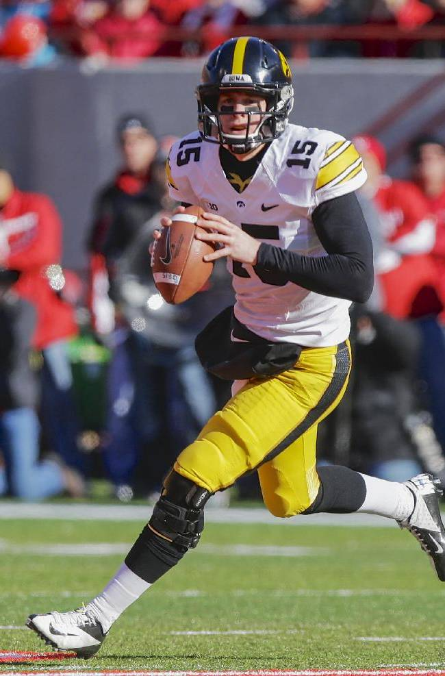 In this Nov. 29, 2013, file photo, Iowa quarterback Jake Rudock rolls out in the first half of an NCAA college football game against Nebraska in Lincoln, Neb. Iowa could rest largely on the shoulders of junior quarterback Rudock in the 2014 season and an offense that too often stalled against elite competition