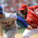 Los Angeles Angels short stop Erick Aybar, right, stretches to tag New York Mets' Travis d'Arnaud, left, in a rundown for an out during the fifth inning of a baseball game in Anaheim, Calif., Sunday, April 13, 2014 The Associated Press