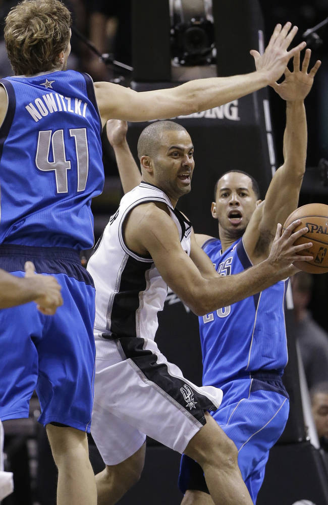 San Antonio Spurs' Tony Parker, center, of France, looks to pass as Dallas Mavericks' Dirk Nowitzki (41), of Germany,  and Devin Harris, right, pressure him during the second half of Game 7 of the opening-round NBA basketball playoff series, Sunday, May 4, 2014, in San Antonio. San Antonio won 119-96
