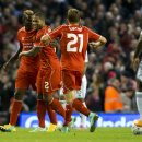 Liverpool's Mario Balotelli, left, celebrates with teammates after scoring against Swansea during the English League Cup soccer match between Liverpool and Swansea at Anfield Stadium, Liverpool, England, Tuesday Oct. 28, 2014