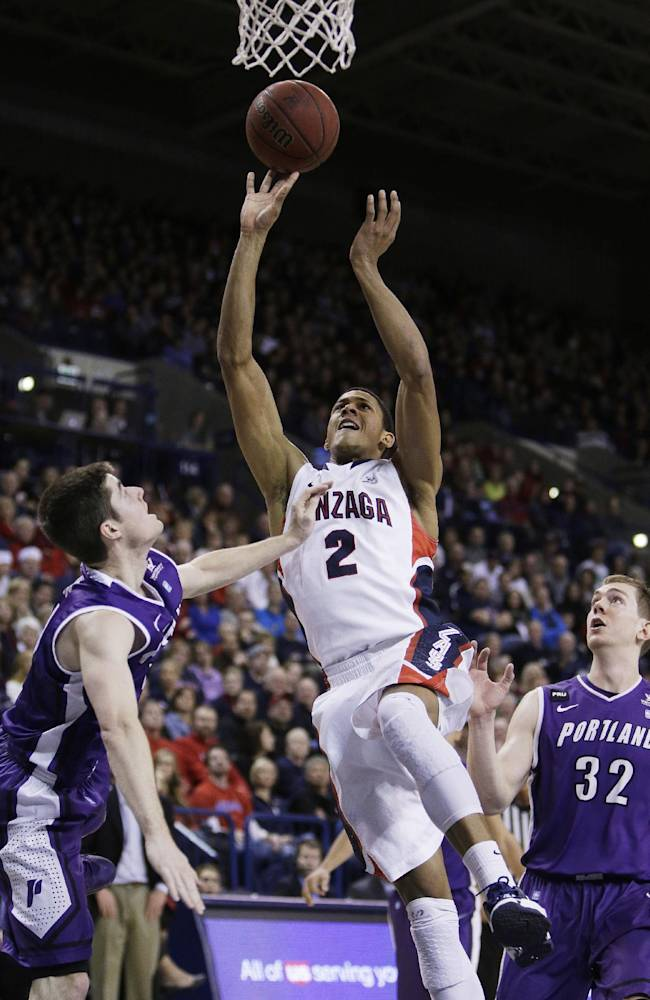 Gonzaga's Angel Nunez (2) attempts a layup between Portland's Ryan Nicholas (32) and Bobby Sharp during the second half of an NCAA college basketball game, on Wednesday, Feb. 5, 2014, in Spokane, Wash. Gonzaga won 71-66