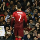 Fans take photos and hold a placard supporting Cristiano Ronaldo of Portugal, a former Manchester United player, during the International Friendly soccer match against Argentina at Old Trafford Stadium, Manchester, England, Tuesday Nov. 18, 2014