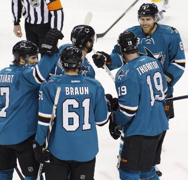 San Jose Sharks' Joe Pavelski, right, celebrates with teammates, from left, Brad Stuart (7), Justin Braun (61), Brent Burns, and Joe Thornton (19) after scoring against the Calgary Flames during the first period of an NHL hockey game, Monday, Jan. 20, 2014 in San Jose, Calif.  The Sharks beat the Flames 3-2