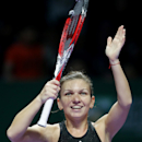 Romania's Simona Halep celebrates after defeating Serena Williams of the U.S. in their singles match at the WTA tennis finals in Singapore,Wednesday, Oct. 22, 2014. (AP Photo/Mark Baker)