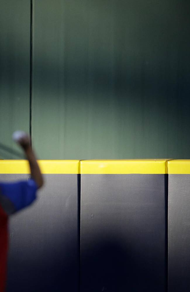 A fan watches from the outfield stands as Philadelphia Phillies' Ethan Martin warms up before the start of a baseball game against the Atlanta Braves, Friday, Sept. 27, 2013, in Atlanta