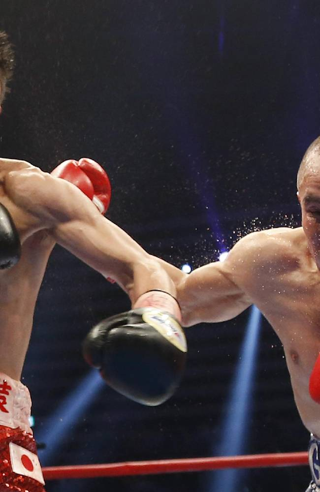 Japanese challenger Naoya Inoue, left, sends a left to Mexican champion Adrian Hernandez during their WBC light flyweight boxing title bout in Tokyo, Sunday, April 6, 2014. Inoue defeated Hernandez by a technical knockout in the sixth round to become the new champion