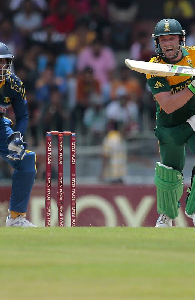 South African one day international team captain AB de Villiers plays a shot as Sri Lankan wicket keeper Kumar Sangakkara watches during the first one-day international cricket match between Sri Lanka and South Africa in Colombo, Sri Lanka, Sunday, July 6, 2014