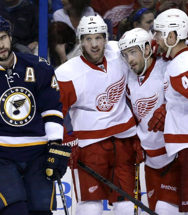 St. Louis Blues' Roman Polak, left, of the Czech Republic, skates past as Detroit Red Wings' Justin Abdelkader is congratulated by teammates Pavel Datsyuk, second from right, of Russia, and Jakub Kindl, right, of the Czech Republic, after scoring during the third period of an NHL hockey game Sunday, April 13, 2014, in St. Louis. The Red Wings won 3-0