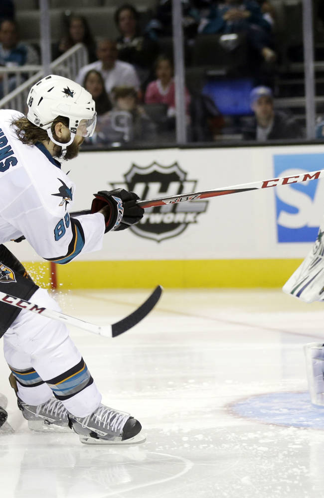 San Jose Sharks's Brent Burns (88) has his shot deflected by Vancouver Canucks goalie Eddie Lack (31) during the third period of a preseason NHL hockey game on Tuesday, Sept. 24, 2013, in San Jose, Calif