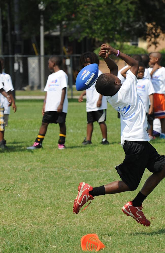 Participants line up for passing drills Saturday, June 21 2014, in Jacksonville, Fla., during the inaugural Mario Butler Football FUNdamentals Camp. Buffalo Bills cornerback Mario Butler and his foundation teamed up with USA Football, a program of NFL Play 60, and other sponsors for the camp