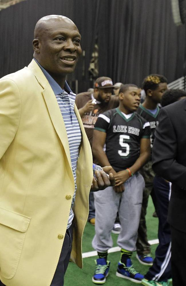 Hall of Fame defensive end Bruce Smith, left, joins newest member Aeneas Williams, right, for a youth punt, pass and kick competition at the inaugural Pro Football Hall of Fame Fan Fest Saturday, May 3, 2014, at the International Exposition Center in Cleveland