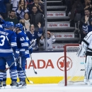 Toronto Maple Leafs teammates celebrate a goal next to Los Angeles Kings goalie Jonathan Quick, right, during third period NHL hockey action in Toronto on Sunday, Dec. 14, 2014 The Associated Press