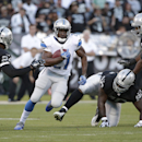 Detroit Lions running back Reggie Bush (21) runs between Oakland Raiders cornerback Charles Woodson (24), defensive tackle Pat Sims (90), and linebacker Nick Roach (53) during the first quarter of an NFL preseason football game in Oakland, Calif., Friday,