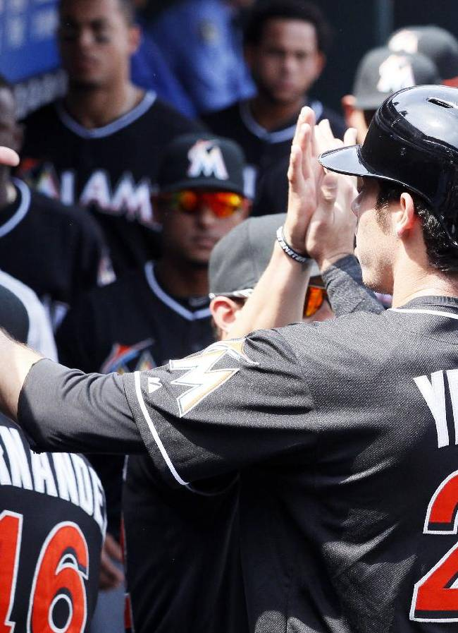 Miami Marlins' Christian Yelich returns to high-fives in the dugout after scoring on a single by teammate Casey McGehee during the first inning of a baseball game against the Philadelphia Phillies, Sunday, April 13, 2014, in Philadelphia