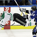 Tampa Bay Lightning right wing J.T. Brown (23) sends Dallas Stars left wing Jamie Benn (14) flying with a check during the third period of an NHL hockey game on Saturday, April 5, 2014, in Tampa, Fla. The Stars won the game 5-2 The Associated Press