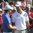 Rory MacIlroy, left, of Northern Ireland shakes hands with Adam Scott of Australia during the trophy presentation of the Australian Open golf tournament in Sydney Sunday, Dec. 1, 2013. MacIlroy was presented the Stonehaven Cup after he defeated Scott by one stroke finishing 18-under par. (AP Photo/Rob Griffith)