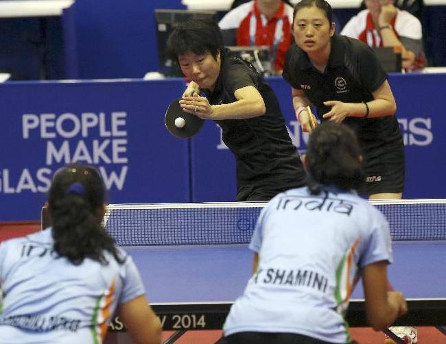 New Zealand's Karen Li, facing left, and Yang Sun serve to India's Shamini Kumaresan and Madhurika Suhas Patkar, left, during their women's doubles table tennis quarterfinal match at the Scotstoun sports center in Glasgow, Scotland, Saturday July 26, 2014
