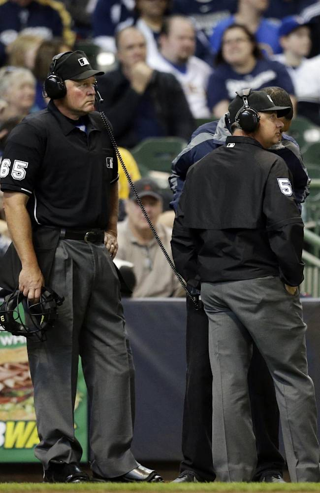 Umpire Ted Barrett (65) listens to the central replay booth in New York in the sixth inning of an opening day baseball game between the Atlanta Braves and Milwaukee Brewers, Monday, March 31, 2014, in Milwaukee. An umpire's call has been overturned for the first time under Major League Baseball's expanded replay system, with Brewers' Ryan Braun ruled out instead of safe