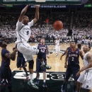 Michigan State's Adreian Payne (5) dunks as Illinois' Brandon Paul, left, Tyler Griffey (42) and Joseph Bertrand (2) and Michigan State's Denzel Valentine, right, watch during the first half of an NCAA college basketball game, Thursday, Jan. 31, 2013, in East Lansing, Mich. (AP Photo/Al Goldis)