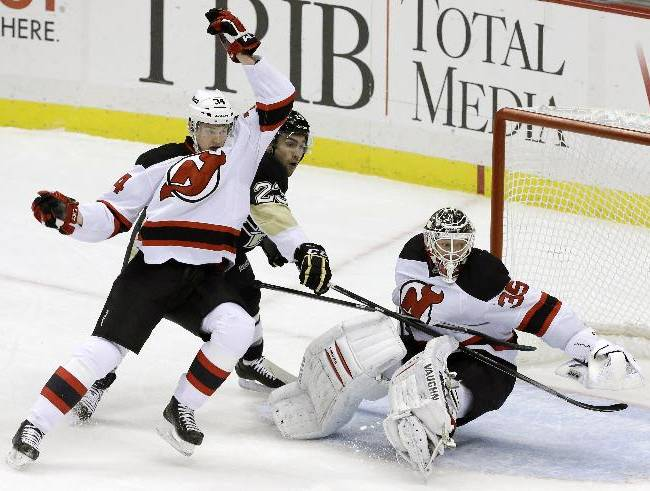 New Jersey Devils' Bryce Salvador, left, collides with Pittsburgh Penguins' Chris Conner (23) in front of New Jersey Devils goalie Cory Schneider (35) during the first period of an NHL hockey game in Pittsburgh, Friday, Dec. 13, 2013