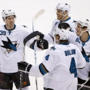 San Jose Sharks' Brenden Dillon (4) celebrates his goal against the Arizona Coyotes with teammates Logan Couture (39), Joe Pavelski (8) and Justin Braun (61) during the third period of an NHL hockey game Tuesday, Jan. 13, 2015, in Glendale, Ariz. The Sha