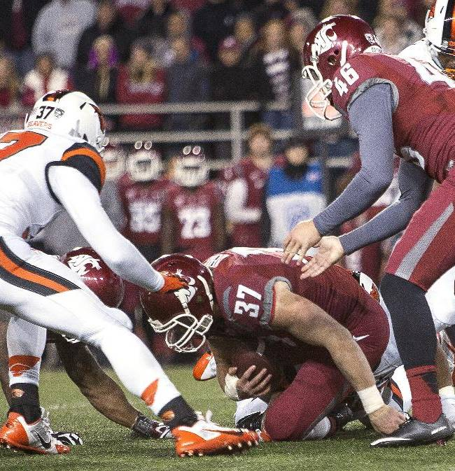 Washington State special teams player Jared Byers, bottom, covers a fumble in front of punter Mike Bowlin (46) at the 27-yard-line on a mis-communicated fake punt attempt as Oregon State's Micah Audiss, left, closes in during the third quarter of an NCAA college football game Saturday, Oct. 12, 2013, at Martin Stadium in Pullman, Wash. Oregon State won 52-24