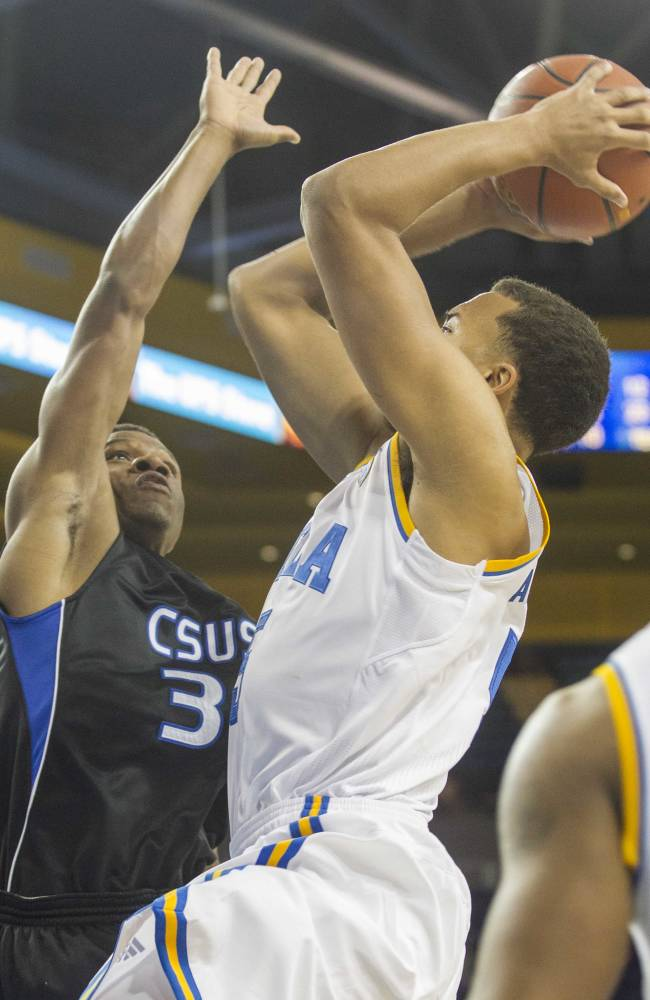 Cal State San Bernardino's Zeke DeBlase, left, tries to block a ball shot by UCLA's Kyle Anderson in the second half of an NCAA college exhibition  basketball game on Wednesday, Oct. 30, 2013, in Los Angeles