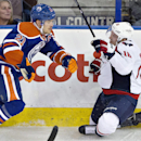 Edmonton Oilers' Andrew Ference, left, his Washington Capitals' Eric Fehr along the boards during the third period of an NHL hockey game in Edmonton, Alberta, on Wednesday, Oct. 22, 2014. The Oilers won 3-2 The Associated Press