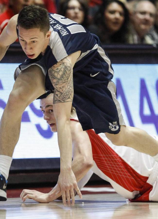 Utah State's Viko Noma'aea, top, and  New Mexico's Hugh Greenwood scramble for the ball during the second half of an NCAA college basketball game, Tuesday, Feb. 25, 2014 in Albuquerque, N.M. New Mexico won 67-58