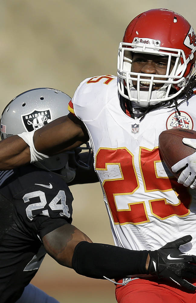 In this Dec. 15, 2013, file photo, Kansas City Chiefs running back Jamaal Charles (25) runs against Oakland Raiders cornerback Charles Woodson during the second quarter of an NFL football game in Oakland, Calif. The NFL revealed Friday, Dec. 27, 2013, that the Chiefs and 49ers each had eight players voted into the Pro Bowl, including running backs Charles of Kansas City and Frank Gore of San Francisco