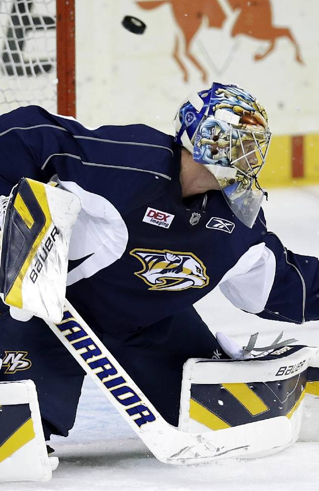 Nashville Predators goalie Pekka Rinne, of Finland, blocks a shot during NHL hockey training camp Thursday, Sept. 12, 2013, in Nashville, Tenn. Rinne had hip surgery May 9 and is expected to sit out the first two preseason games