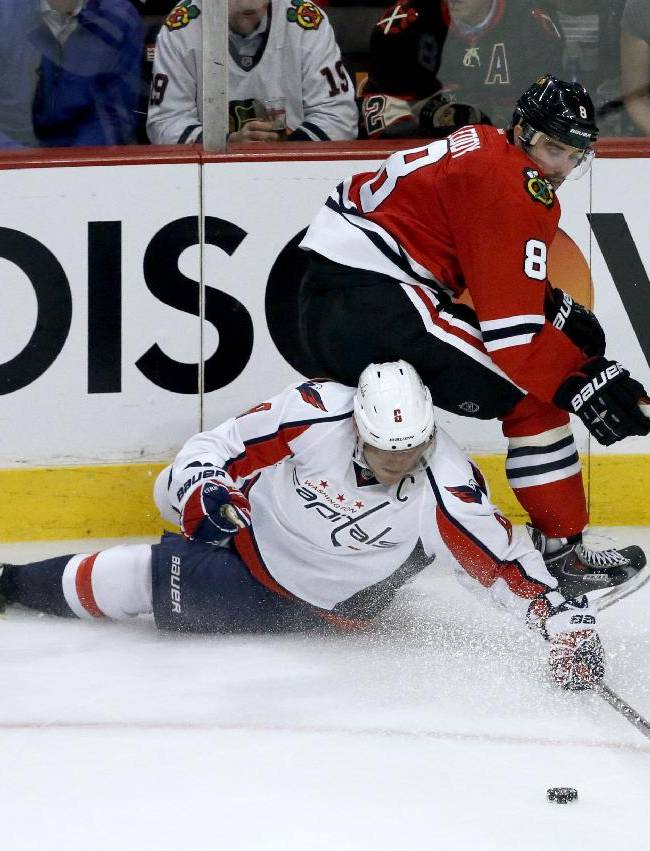 Washington Capitals right wing Alex Ovechkin, left, and Chicago Blackhawks defenseman Nick Leddy compete for a loose puck during the third period of an NHL hockey game Tuesday, Oct. 1, 2013, in Chicago. The Blackhawks won 6-4