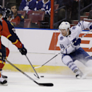 Toronto Maple Leafs right wing Phil Kessel (81) goes for the puck as Florida Panthers defenseman Dmitry Kulikov (7) and defenseman Brian Campbell (51) defend in the first period of an NHL hockey game on Thursday, April 10, 2014, in Sunrise, Fla. The Panth