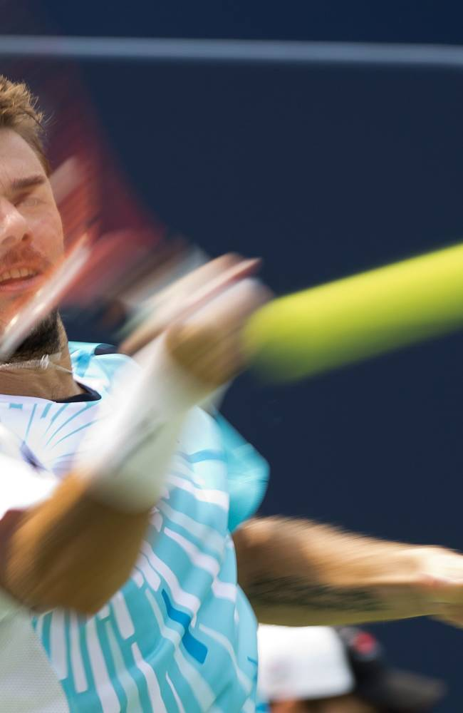 Stan Wawrinka,  of Switzerland, make a returns against Kevin Anderson, of South Africa, during a men's third round match at the Rogers Cup tennis tournament action in Toronto Thursday, Aug. 7, 2014