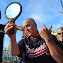 Atlanta Braves pitcher Kris Medlen checks out his new looks after having his head shaved to help raise awareness and funding for cancer research at baseball spring training camp on Wednesday, Feb. 19, 2014, in Kissimmee Fla The Associated Press