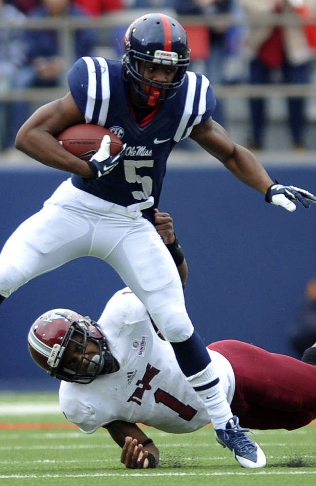 Mississippi running back I'Tavius Mathers (5) is tackled by Troy safety Camren Hudson (1) during an NCAA college football game in Oxford, Miss., Saturday, Nov. 16, 2013