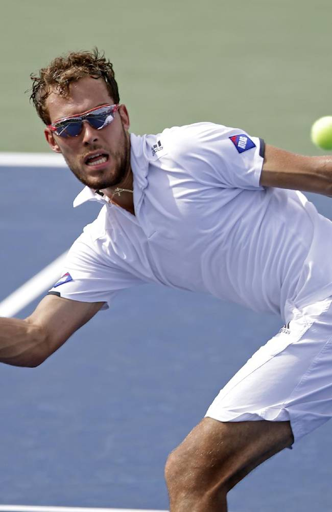 CORRECTS TO GOFFIN NOT GOFFEN  - Jerzy Janowicz, of Poland, returns a shot to David Goffin, of Belgium, in their match at the Winston-Salem Open tennis tournament in Winston-Salem, N.C., Thursday, Aug. 21, 2014