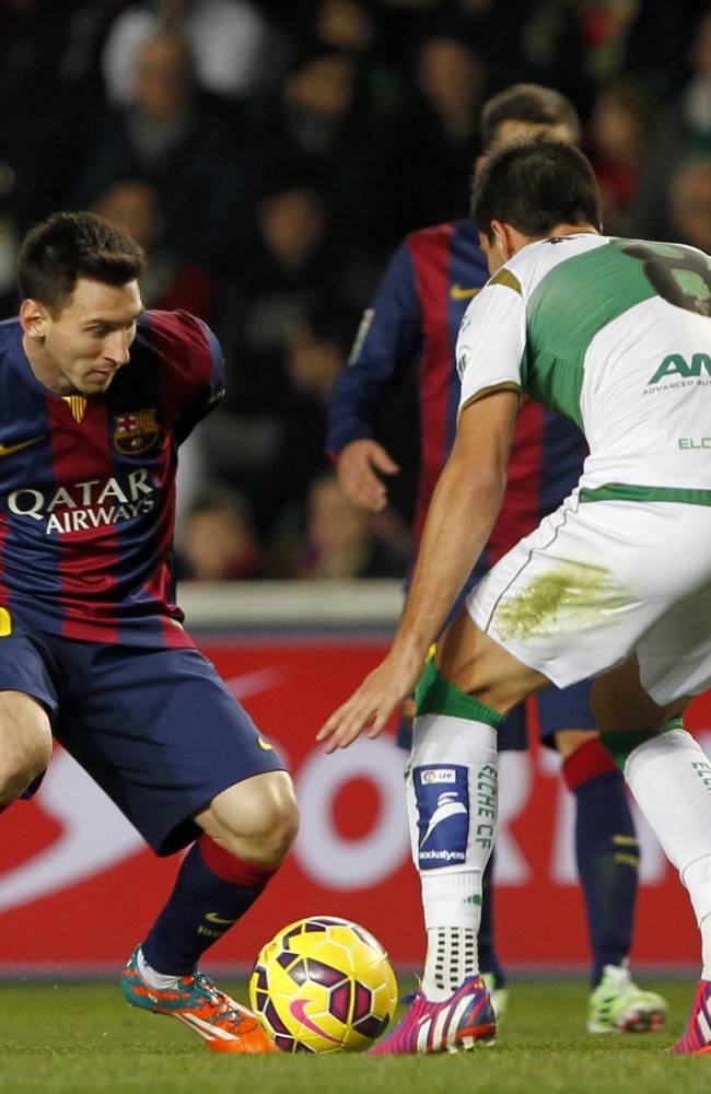 Barcelona's Lionel Messi, from Argentina, left, duels for the ball with Elche's Adrian Gonzalez, during a Spanish La Liga soccer match between Elche and Barcelona, at the Martinez Valero stadium in Elche, Spain, Saturday, Jan. 24, 2015. Barcelona won the match 6-0