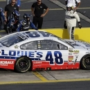 A crew member for Jimmie Johnson (48) pushes the car back as Johnson overshoots his pit area during a stop while qualifying for Saturday's NASCAR Sprint Cup Series All-Star auto race at Charlotte Motor Speedway in Concord, N.C., Friday, May 17, 2013. (AP Photo/Gerry Broome)