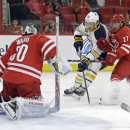 Carolina Hurricanes goalie Cam Ward (30) and teammate Justin Faulk (27) defend Buffalo Sabres' Marcus Foligno (82) during the second period of a preseason NHL hockey game in Raleigh, N.C., Friday, Oct. 3, 2014 The Associated Press