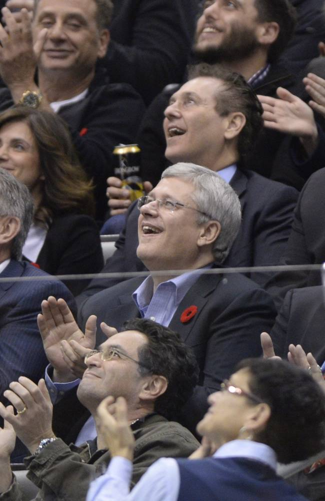 Maple Leaf Sports and Entertainment CEO and president Tim Leiweke, Prime Minister Stephen Harper and legendary former NHL coach Scotty Bowman cheer as they look at the video display board during the first period of an NHL hockey game, Friday, Nov. 8, 2013 in Toronto