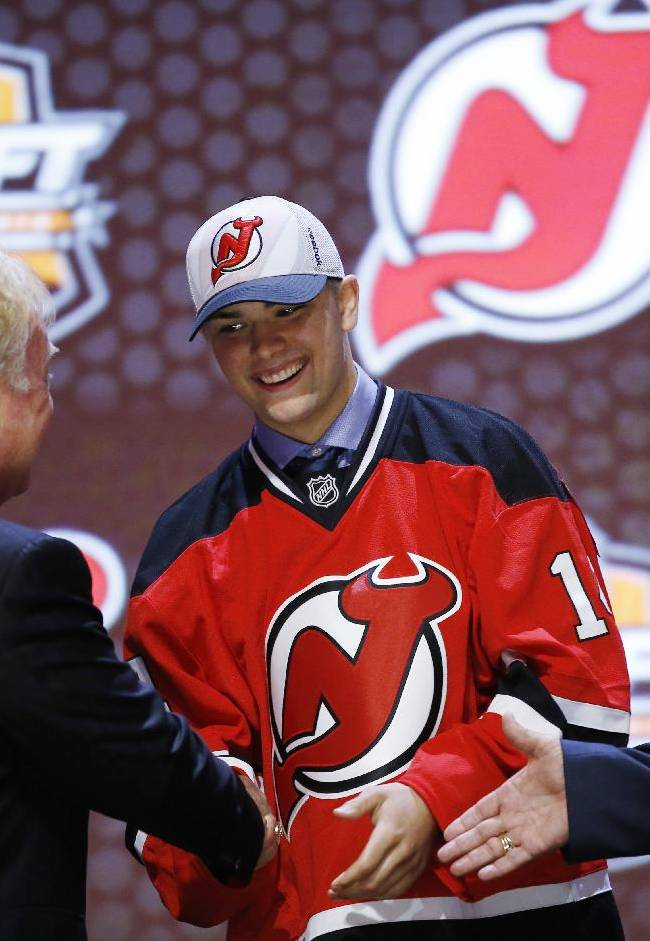 John Quenneville shakes hands with New Jersey Devils officials after being chosen 30th overall during the first round of the NHL hockey draft, Friday, June 27, 2014, in Philadelphia