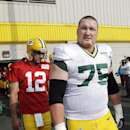 In this July 28, 2014, file photo, Green Bay Packers' Aaron Rodgers and Bryan Bulaga (75) walk on the field for NFL football training camp in Green Bay, Wis. A little lost in the hand-wringing over the loss of center J.C. Tretter is the return of right ta