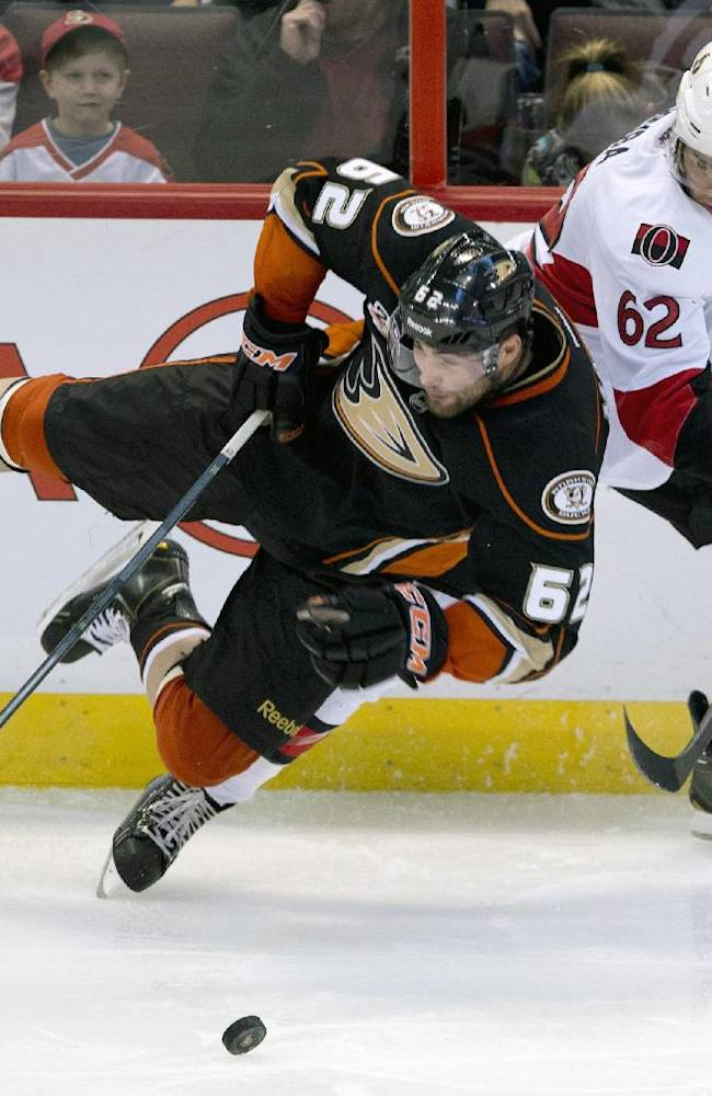 Anaheim Ducks left wing Patrick Maroon tries to play the puck as he collides with Ottawa Senators defenseman Eric Gryba during the third period of an NHL hockey game,  Friday Oct. 25, 2013 in Ottawa, Ontario. The Ducks defeated the Senators 2-1