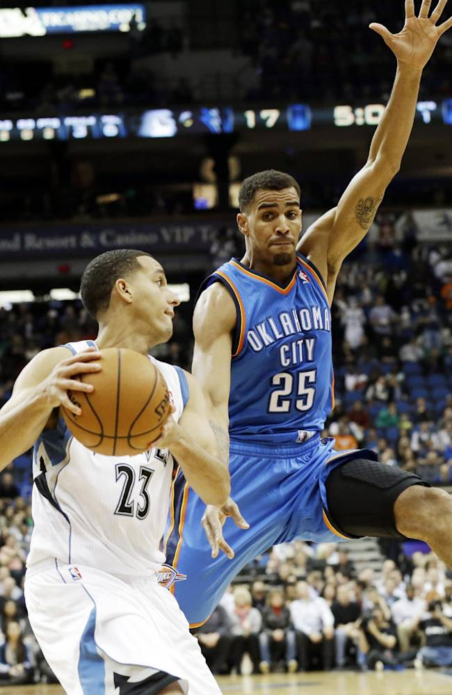Oklahoma City Thunder's Thabo Sefolosha, right, of Switzerland, looms over Minnesota Timberwolves' Kevin Martin in the first quarter of an NBA basketball game, Friday, Nov. 1, 2013 in Minneapolis