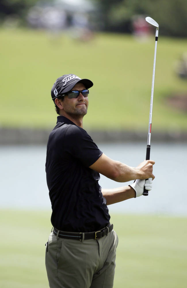 Adam Scott of Australia, reacts to his shot from the 18th fairway during the third round of The Players championship golf tournament at TPC Sawgrass, Saturday, May 10, 2014, in Ponte Vedra Beach, Fla
