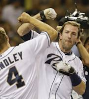 San Diego Padres' Chris Denorfia and Nick Hundley celebrate after Denorfia's two-run walk off home run gave the Padres a 2-1 victory over the Cincinnati Reds in the bottom of the ninth inning of a baseball game in San Diego, Monday, July 29, 2013. (AP Photo/Lenny Ignelzi)