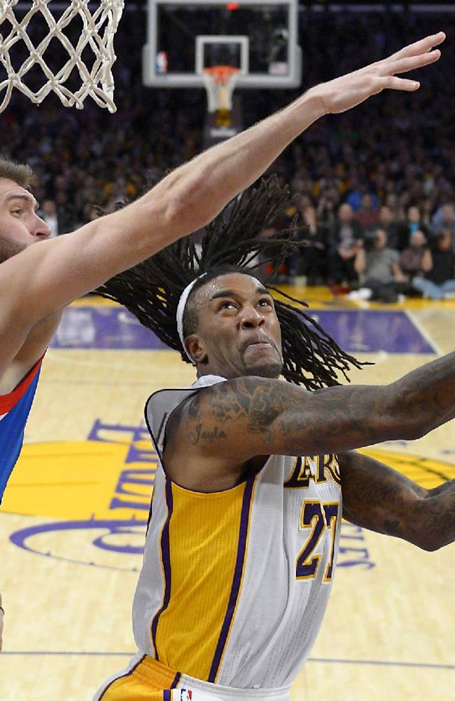 Los Angeles Lakers center Jordan Hill, center, puts up a shot as Philadelphia 76ers center Spencer Hawes defends during the second half of an NBA basketball game, Sunday, Dec. 29, 2013, in Los Angeles