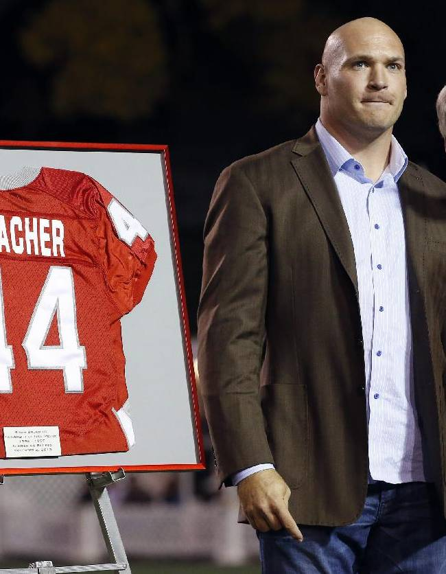 Former New Mexico and Chicago Bears football player Brian Urlacher, left, stands next to New Mexico Vice President for Athletics Paul Krebs as Krebs points to the press box area where Urlacher's name and number is displayed as his jersey number is retired during a halftime ceremony at an NCAA college football game against the Air Force on Friday, Nov. 8, 2013, in Albuquerque, N.M